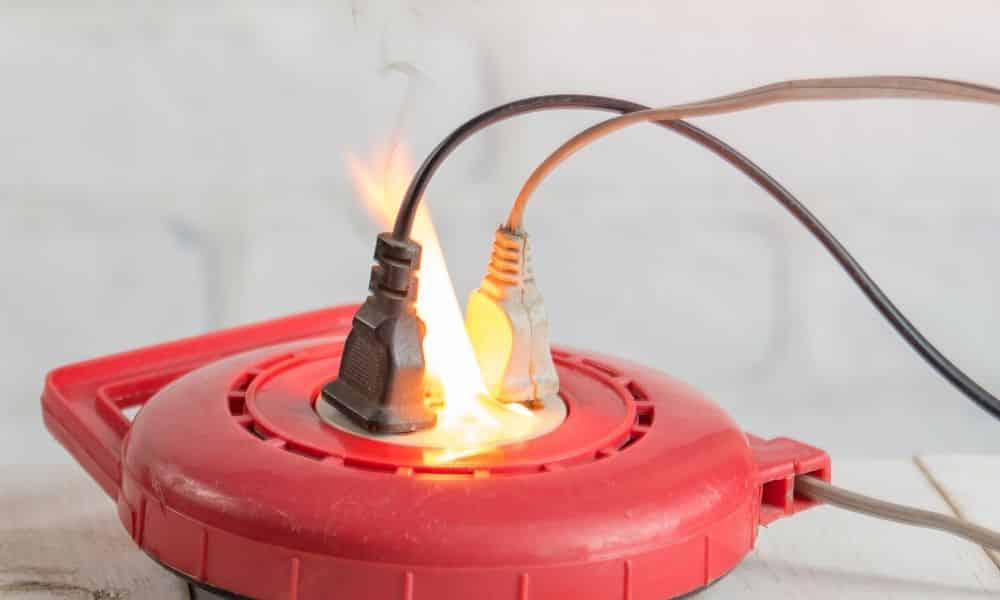 An electrical fire at the outlet of a power cable.